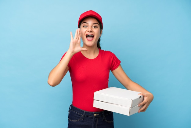 Young woman holding a pizza wall shouting with mouth wide open