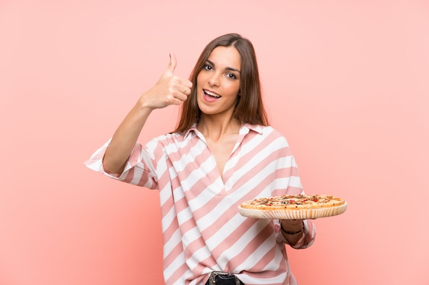 Young woman holding a pizza with thumbs up because something good has happened