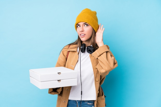 Young woman holding pizzas trying to listening a gossip