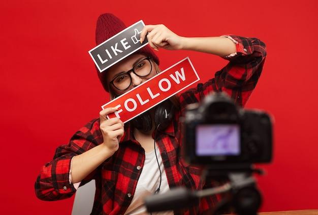 Молодая женщина держит плакаты перед лицом и снимает видео для своих последователей