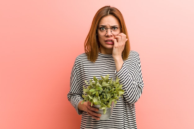 Young woman holding a plant biting fingernails, nervous and very anxious.
