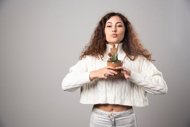 Giovane donna che tiene una pianta su un muro grigio. foto di alta qualità