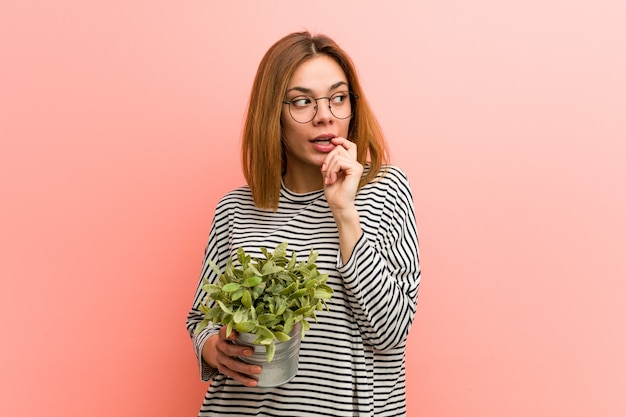 Young woman holding a plant relaxed thinking about something looking at a copy space.