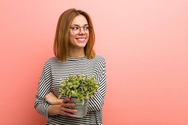 Young woman holding a plant smiling confident with crossed arms.