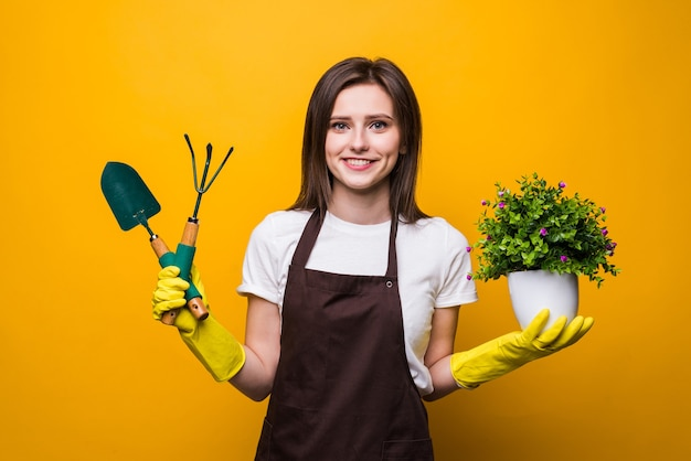 Young woman holding a plant and tools isolated