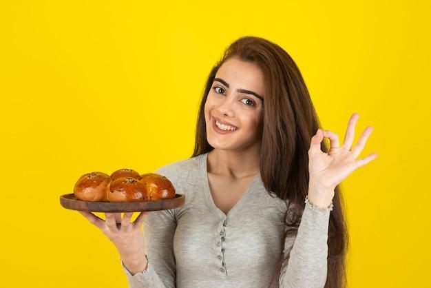 노란색 벽 위에 신선한 과자 접시를 들고 젊은 여자.