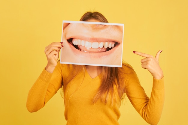 Young woman holding pointing finger at picture of mouth smiling showing her teeth on yellow background. dentist concept
