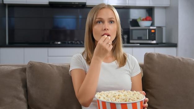 Молодая женщина держит коробку попкорна и смотрит телевизор.