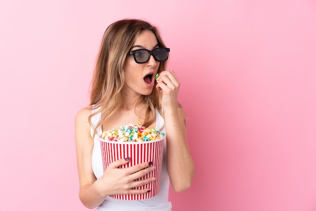 Young woman holding popcorns over isolated wall
