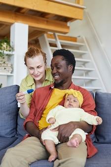 Молодая женщина держит тест на беременность и показывает его своему мужу, пока он сидит на диване с ребенком