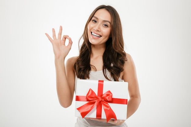 Young woman holding present box with red bow and showing ok sign, isolated over white