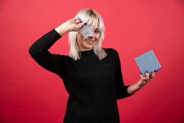 Giovane donna che tiene un regalo con una stella su una parete rossa.