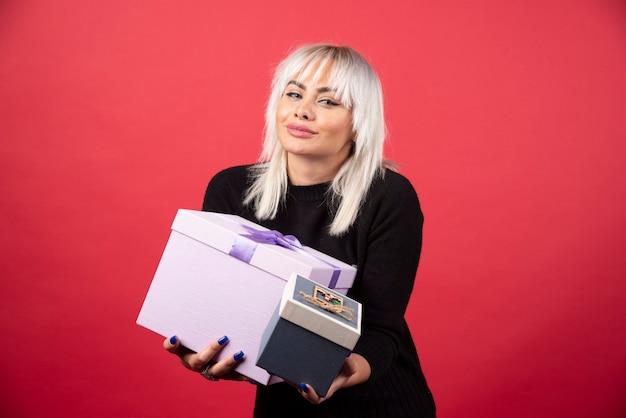 Giovane donna che tiene i regali su una parete rossa.