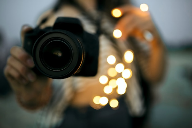Young woman holding professional digital photo camera with bokeh light