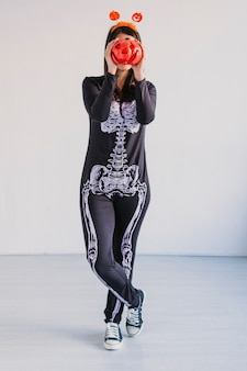 Young woman holding a pumpkin covering her face. wearing a black and white skeleton costume. halloween concept. indoors. lifestyle