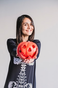 Young woman holding a pumpkin and smiling. wearing a black and white skeleton costume. halloween concept. indoors. lifestyle
