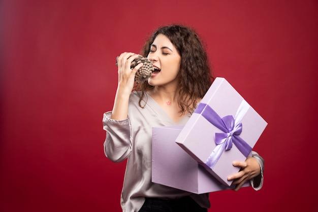 보라색 선물 상자를 누르고 pinecone를 물고 젊은 여자.