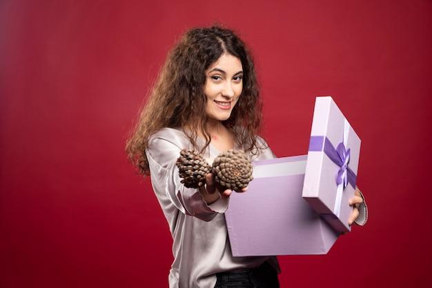 보라색 선물 상자와 pinecones를 들고 젊은 여자.