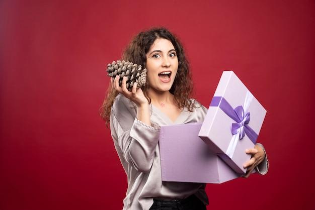 Giovane donna che tiene confezione regalo viola e pigne nelle quali.