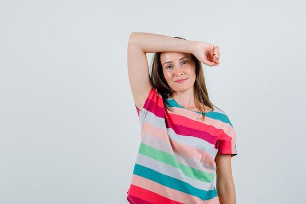 Tシャツで額に上げられた腕を保持し、陽気に見える若い女性、正面図。