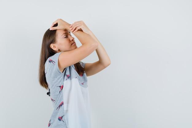 T- 셔츠에 머리에 제기 손을 잡고 피곤 찾고 젊은 여자. 전면보기.