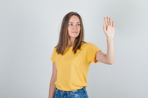 上げられた手を開いて、tシャツで笑っている若い女性