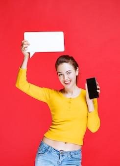 Giovane donna con in mano una scheda informativa rettangolare e uno smartphone nero