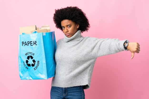 Young woman holding a recycle bag isolated on colorful showing thumb down with negative expression