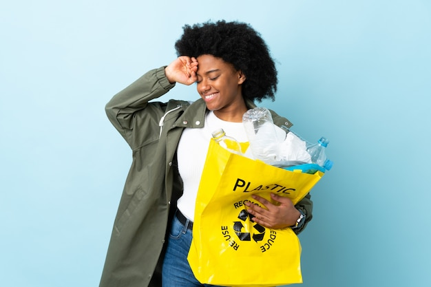 Young woman holding a recycle bag isolated on colorful with tired and sick expression