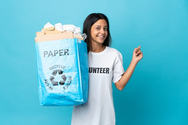 Young woman holding a recycling bag full of paper pointing back
