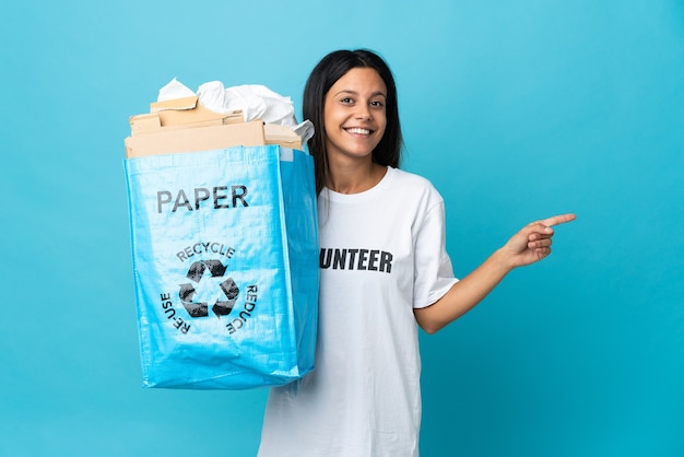 Young woman holding a recycling bag full of paper pointing finger to the side