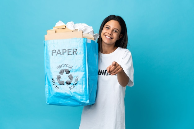 Young woman holding a recycling bag full of paper pointing front with happy expression