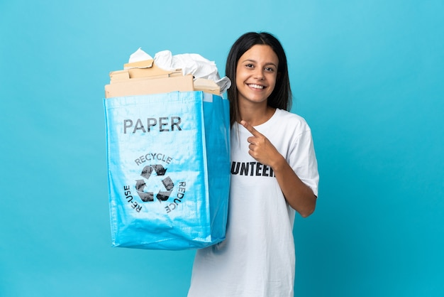 Young woman holding a recycling bag full of paper pointing to the side to present a product