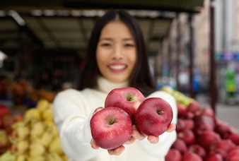 市場の店で手に赤いリンゴを保持している若い女性
