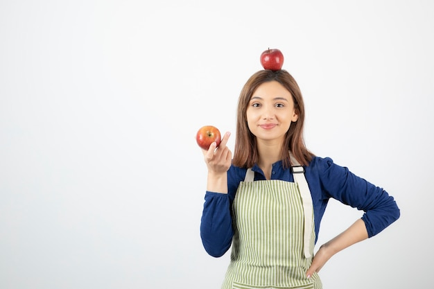 Young woman holding red apples while smiling on white background.