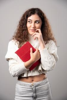 회색 벽에 빨간 책을 들고 젊은 여자. 고품질 사진