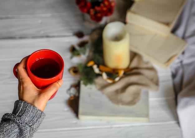 彼女の寝室でお茶の赤いカップを保持している若い女性