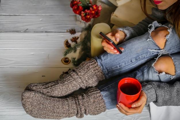 Giovane donna che tiene tazza rossa di tè nella sua camera da letto