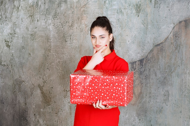 Young woman holding a red gift box with white dots on it and looks thoughtful.