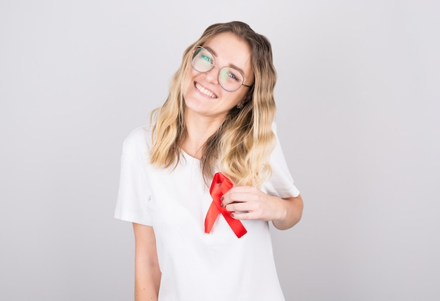 Young woman holding red gold ribbon awareness symbol for endometriosis, suicide prevention, sarcoma bone cancer, bladder cancer, liver cancer and childhood cancer concept.