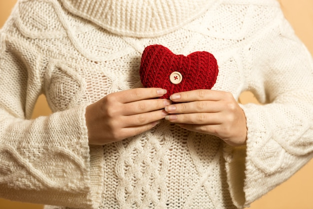 Young woman holding red heart on chest
