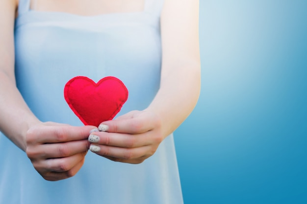 Young woman holding a red heart in her hands on blue