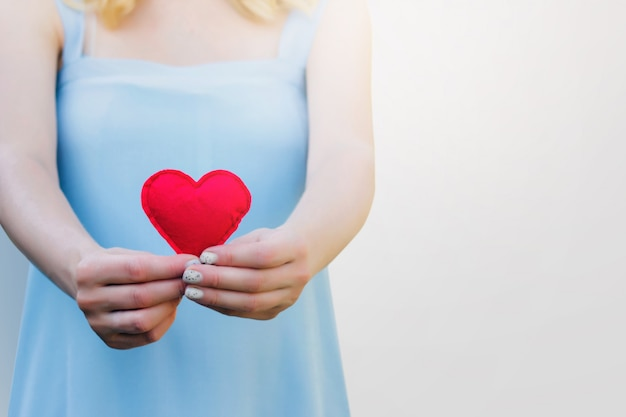 Young woman holding a red heart in her hands on white