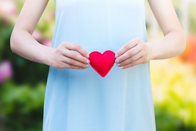 Young woman holding a red heart in her hands