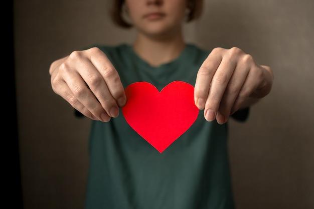 Молодая женщина держит в руках красное сердце. медицинское страхование, концепция пожертвований и благотворительности, всемирный день сердца, фото справедливой торговли