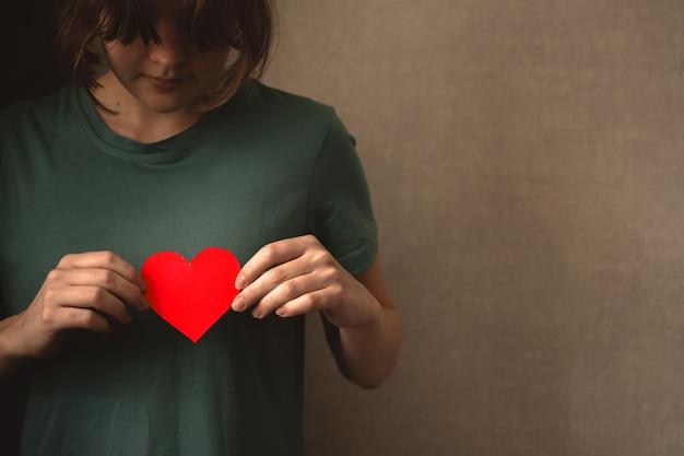 그녀의 가슴에 붉은 마음을 들고 젊은 여자. 자선과 사랑, 생명 보험 및 세계 정신의 날의 개념. 복사 공간 사진