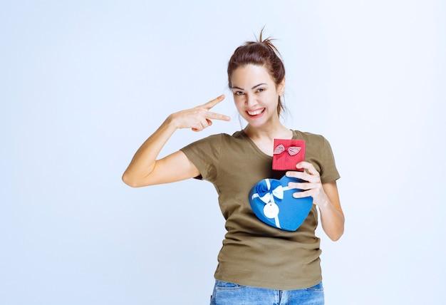 Giovane donna che tiene scatole regalo rosse e blu a forma di cuore e le gode