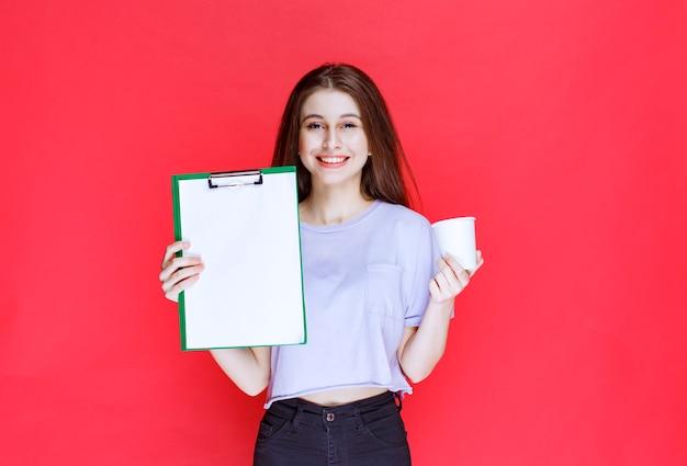 보고서 시트와 음료 한 잔을 들고 젊은 여자.