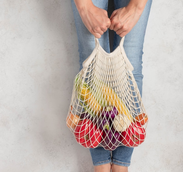 Young woman holding a reusable mesh bag with fresh vegetables. light . zero waste .