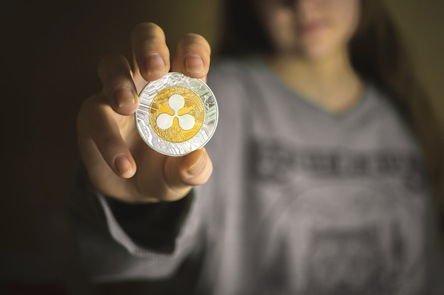 Young woman holding ripple coin, cryptocurrency business background photo